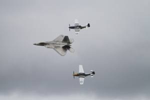 F-22 flanked by two vintage P-51 Mustangs
