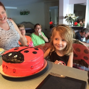 The birthday girl and her ladybug cake and wings